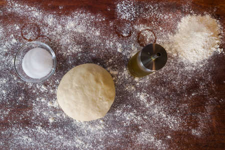 Dough for pizza over a wooden table seen from above