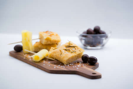 Italian focaccia with rosemary, olives and cheese over a cutting board