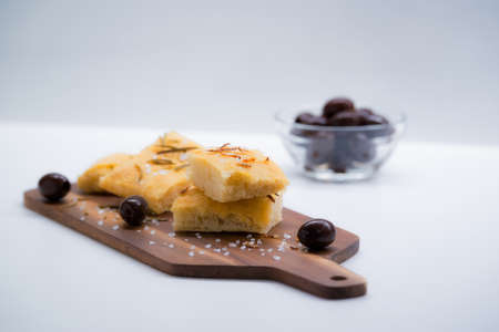 Italian focaccia with onion and olives over a cutting board
