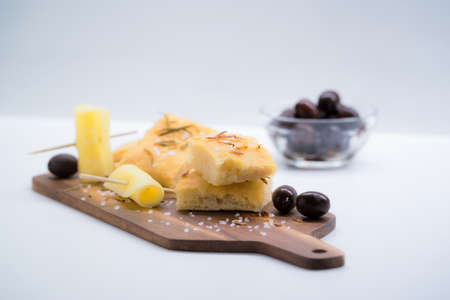 Italian focaccia with onion, olives and cheese over a cutting board