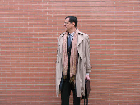 Outstanding businessman with briefcase and coat