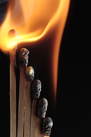 combustion of several matchsticks on black background