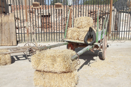 old farm: old farm wagon with some hay bales
