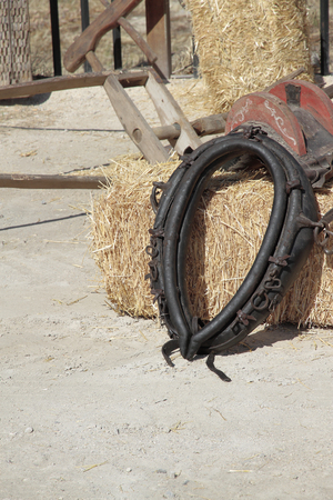 farm implements: black leather yoke over a hay bale