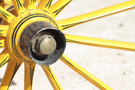 yelow: detail of an antique yelow cart wheel