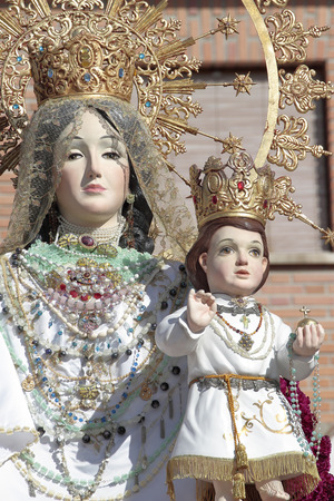 virgin mary mother of god: statue virgin del Rosario with baby Jesus in the town of Torrejon de Ardoz during a outdoor flower offering that occurs every year on month of Octuber