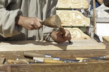 forefront: forefront of hands of a wood sculptor carving wood
