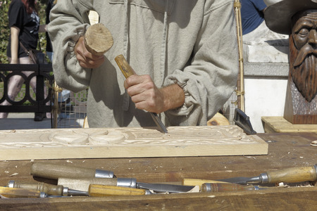 sculptor: forefront of hands of a wood sculptor carving wood