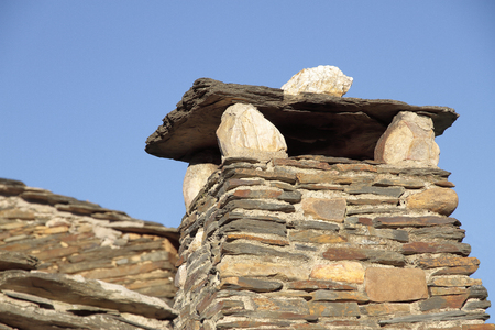 flue: chimney flue outlet made of slate on a construction typical of the villages of black architecture in the province of Guadalajara-Spain