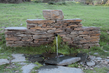 jet stream: fountain made with slate bricks. Slate is typical of the villages of black architecture in the province of Guadalajara-Spain