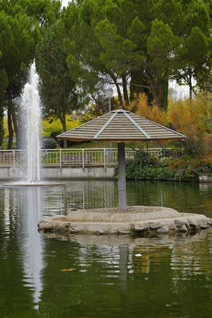 recreational area: umbrella and fountain in the pond of a recreational area in the city of Coslada in the province of Madrid-Spain Stock Photo