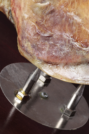 cured ham: close up of a part of a Spanish cured ham on their ham holder Stock Photo