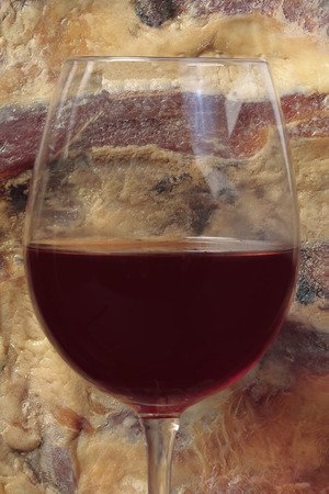 cured ham: red wine glass with spanish cured ham as background