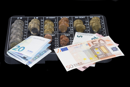 forefront: forefront of a euro coins organizer with coins and some euro bills on black background