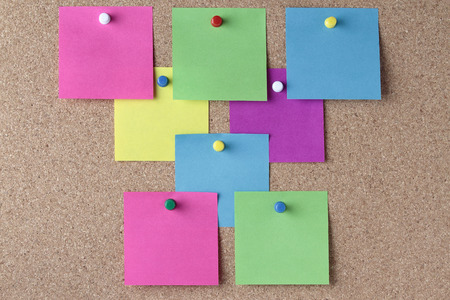 push in pins: background of colored notes with colored push pins on a cork pinboard