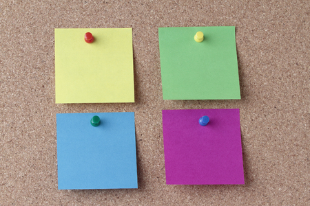 push in pins: four colored notes with colored push pins on a cork board
