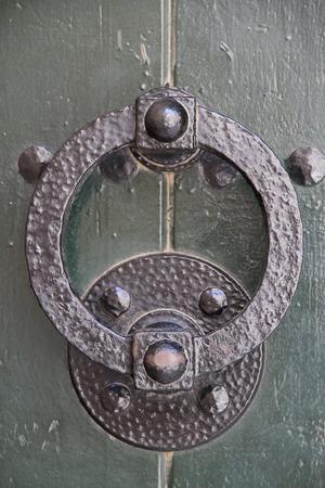 iron doorknocker on a old green wooden door Stock Photo