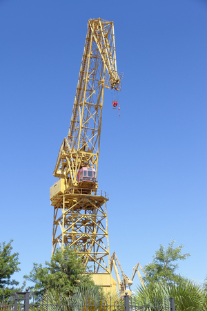 foreground of a yellow color harbor crane with the sky as background