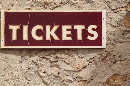 rectangular red signboard that indicates the sale of tickets on a wall of stone