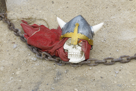 horizontal composition with a skull with medieval helmet on a sandy floor