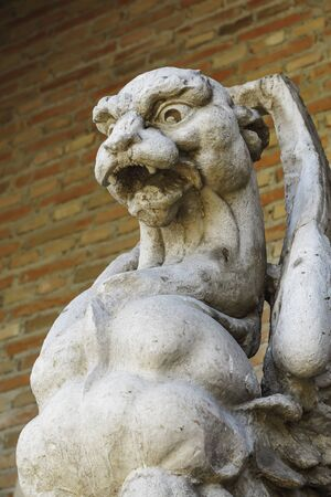 detail in foreground of an ancient gargoyle carved in stone