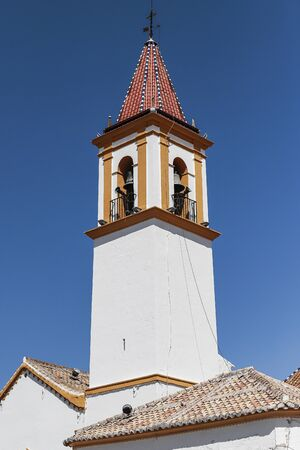 foreground of bell tower of the immaculate conception church in the spanish municipality of Sierra de Yeguas in the province of malaga with blue sky as background 写真素材