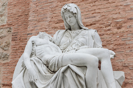 foreground detail of a replica of Miguel Angel famous sculpture the Pieta at Adolfo Suarez park of Torrejon de Ardoz, madrid, spain with wall of bricks as background