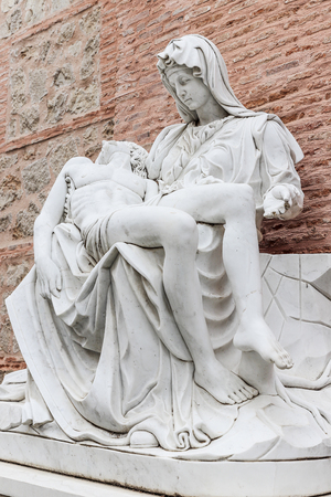 side view of a replica of Miguel Angel famous sculpture the Pieta at Adolfo Suarez park of Torrejon de Ardoz, madrid, spain with wall of bricks as background