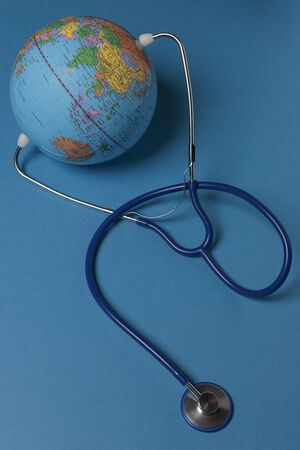 vertical view of terrestrial globe with a stethoscope on blue background Foto de archivo