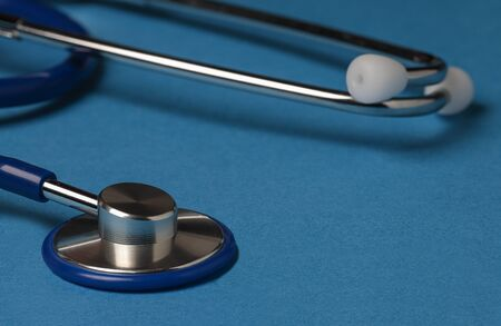 vertical view of an stethoscope with the bell on foreground on blue background Banco de Imagens