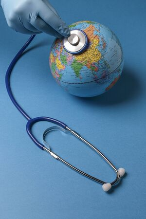 vertical view of a hand with nitrile blue glove using a stethoscope to auscultate the terrestrial globe on blue background