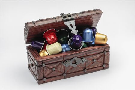 horizontal view of a wooden chest with several espresso coffee capsules isolated on white background