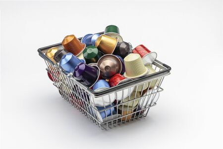 horizontal view of an aluminum basket with several espresso coffee capsules isolated on white background