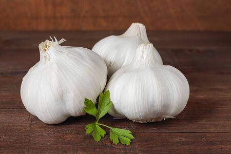 horizontal view of three garlic heads and parsley leaves on a table and wood background