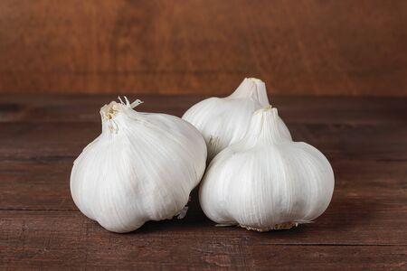 horizontal view of three garlic heads on a table and wood background Zdjęcie Seryjne