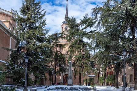 horizontal view of bernardas square in the city of alcala de henares after a snowfall with the convent of saint bernard in the background on a sunny day and cloudy blue sky
