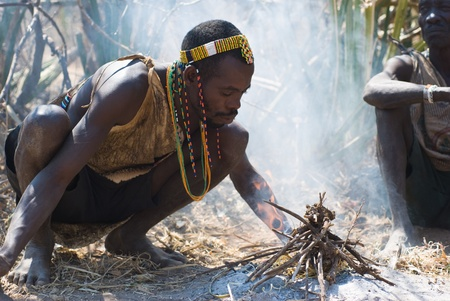 LAKE EYASI, TANZANIA, AUGUST 14, 2010: an unidentified man from Hdza tribe light a fire as they did thousands of years ago. Hdza tribe is an ethnic group in north Tanzania