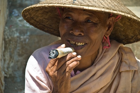 cheroot: MINGUN, MYANMAR-AUGUST 17, 2007: unidentified nun smoking a big cheroot in Mingun, near Mandalay, August 17, 2007. A cheroot is a cigar made principally by dried fruits and little bit of tobacco