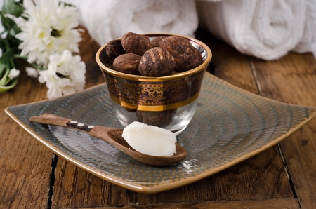 Shea butter in a spoon and nuts. Spa mood Stock Photo