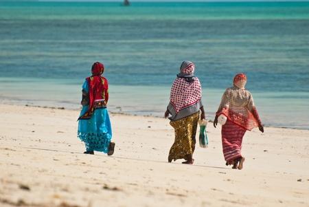 zanzibar: Vrouwen lopen op het strand in de kleurrijke jurken