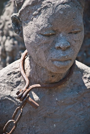 Statue of a woman in slavery posed in Stone Town, Zanzibar, where once was placed the slave market. Stock Photo