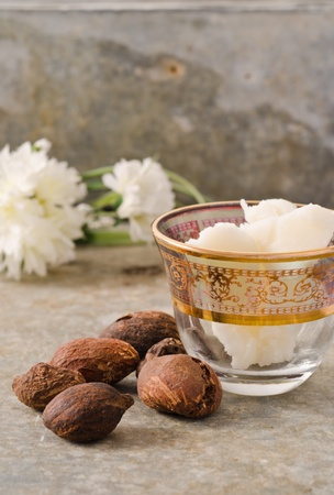 shea butter: Shea nuts still life with a Moroccan glass filled with shea butter