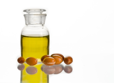 A bottle of argan oil and some argan fruits on white. Argan oil is used for cosmetic products Stock Photo