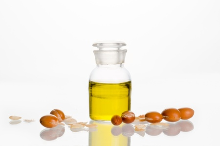 Argan oil with fruits on white background. Argan comes from Morocco and is used in cosmetic products Stock Photo