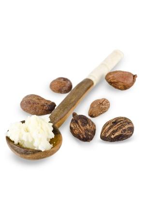 mantequilla: cuchara de madera con manteca de karit� tuercas sobre fondo blanco y manteca de karit�