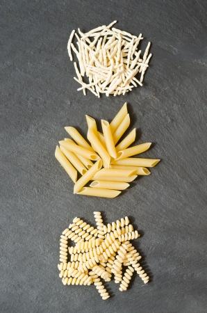 fusilli: three kind of italian dried pasta on a black natural stone Stock Photo
