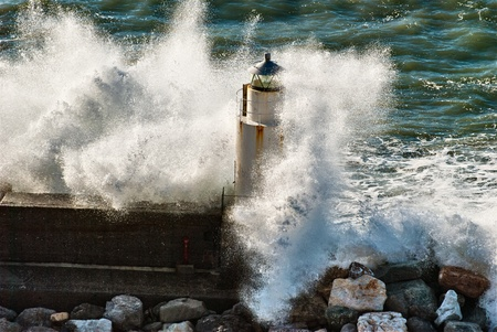 Waves breaking against a lighthouse in Italy photo