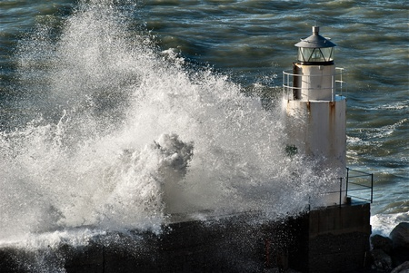 wind storm: Waves breaking against a lighthouse in Italy