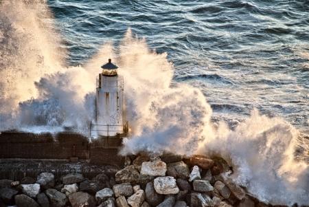 paisaje mediterraneo: Las olas rompiendo contra un faro en Italia Foto de archivo