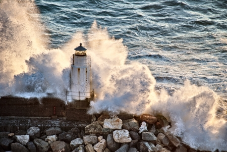 strong wind: Waves breaking against a lighthouse in Italy